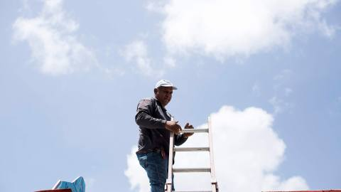 Noel Torres works at Cl'nica Iella in San Juan, P.R., on July 5, 2018. Torres installs solar power systems in the island and has seen more work after hurricane Maria struck in September of last year, and left the American territory in the dark. The clinicÕs new solar system, funded by Direct Relief, will help them maintain their medication if thereÕs power interruption. Torres, from Aguadilla, worked for months installing solar panels while not having power for his family at home. (Erika P. Rodriguez/Direct Relief)