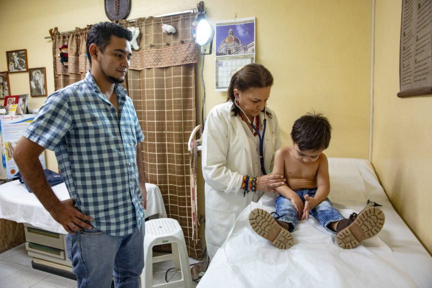 Doctor Madrid visit a child while his father attends, at the ruth Paz clinic in San Pedro Sula, where various services are provided:various services: general medicine, dentistry, and orthodontics. (Photo by Francesca Volpi for Direct Relief)