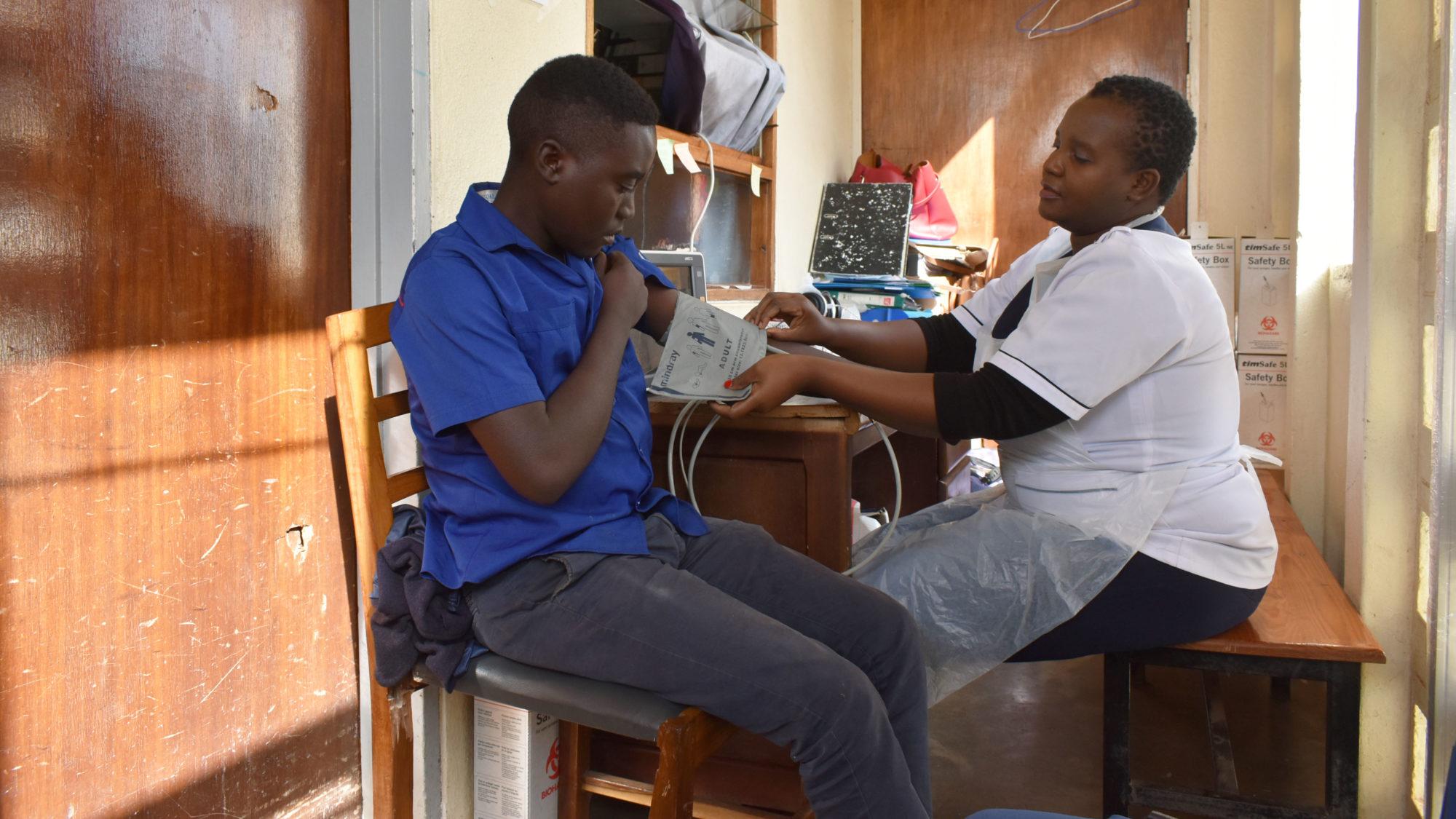 Asekanadziwa Mtangwanika, a nurse, takes a cancer patient's blood pressure at Kamuzu Central Hospital in Lilongwe, Malawi. (Photo courtesy of UNC Project Malawi)