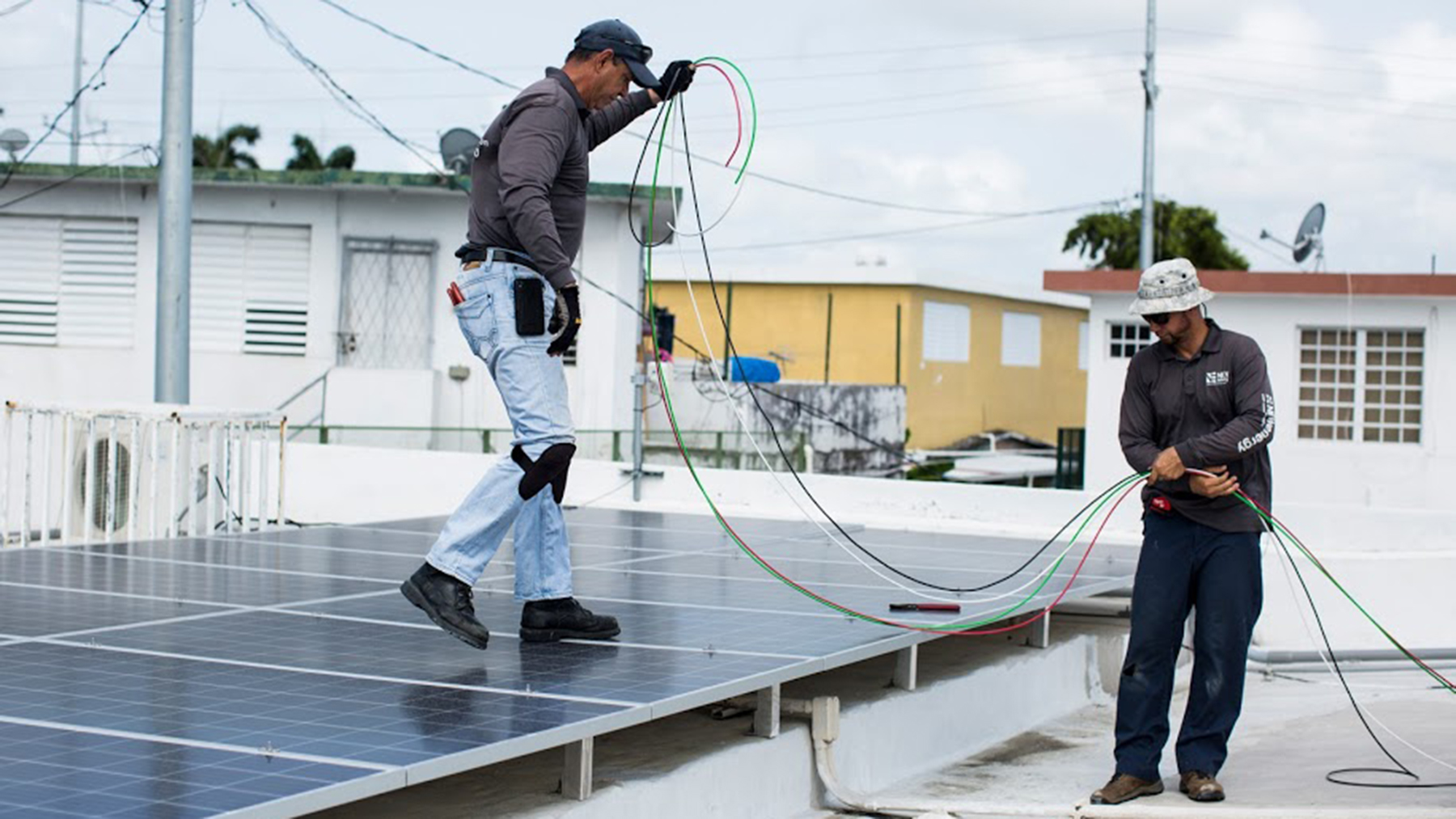 From left, brothers Luis Montalvo and Jared Montalvo install a solar power system at Clínica Iella in San Juan, P.R., on July 5, 2018. Solar power can keep a clinic operational during a disaster and protect vital medicines. (Erika P. Rodriguez/Direct Relief)