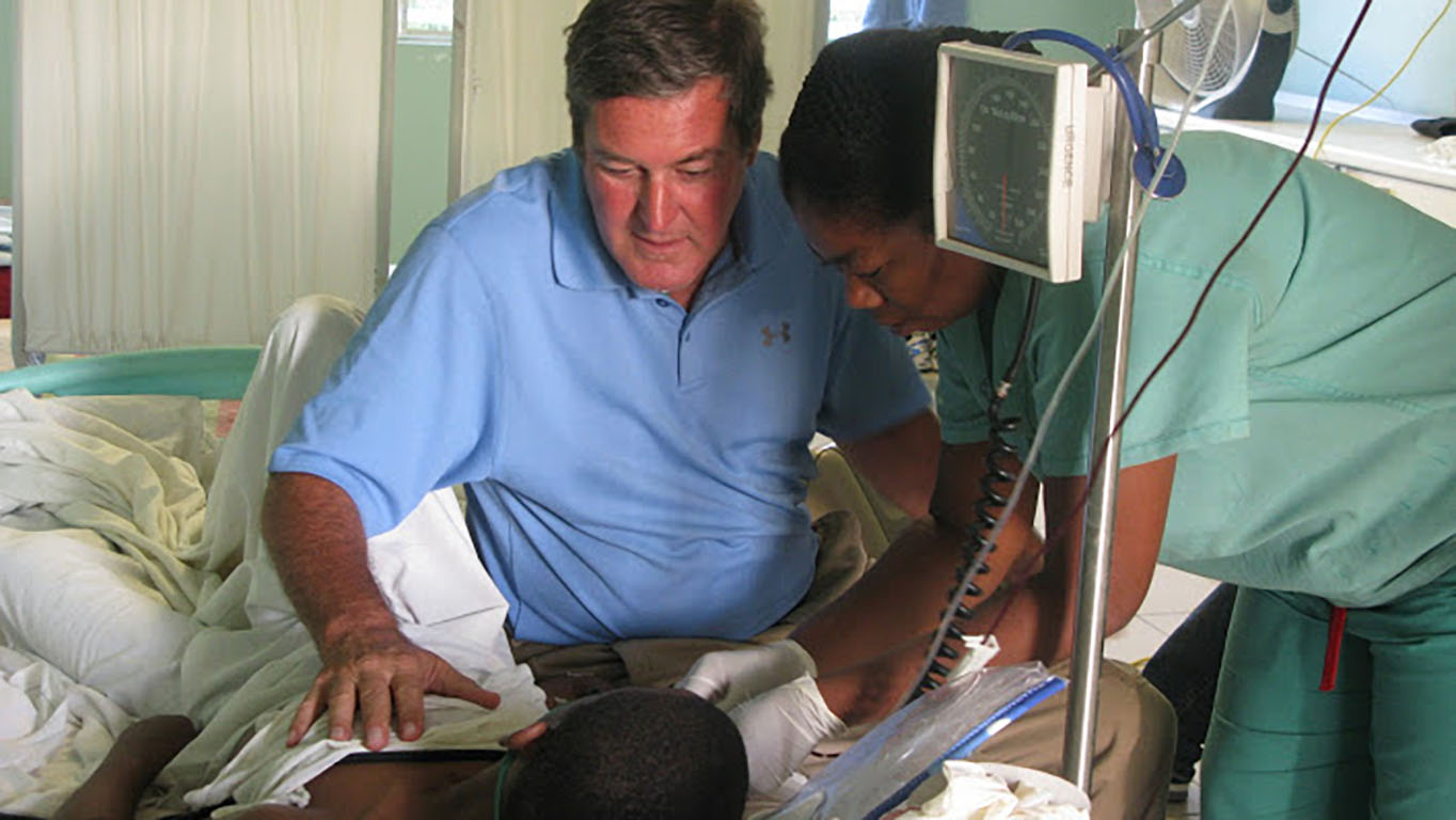 Father Rick Frechette tends to a patient at St. Luke's Hospital in Port au Prince, Haiti. (Photo courtesy of St. Luke Foundation)
