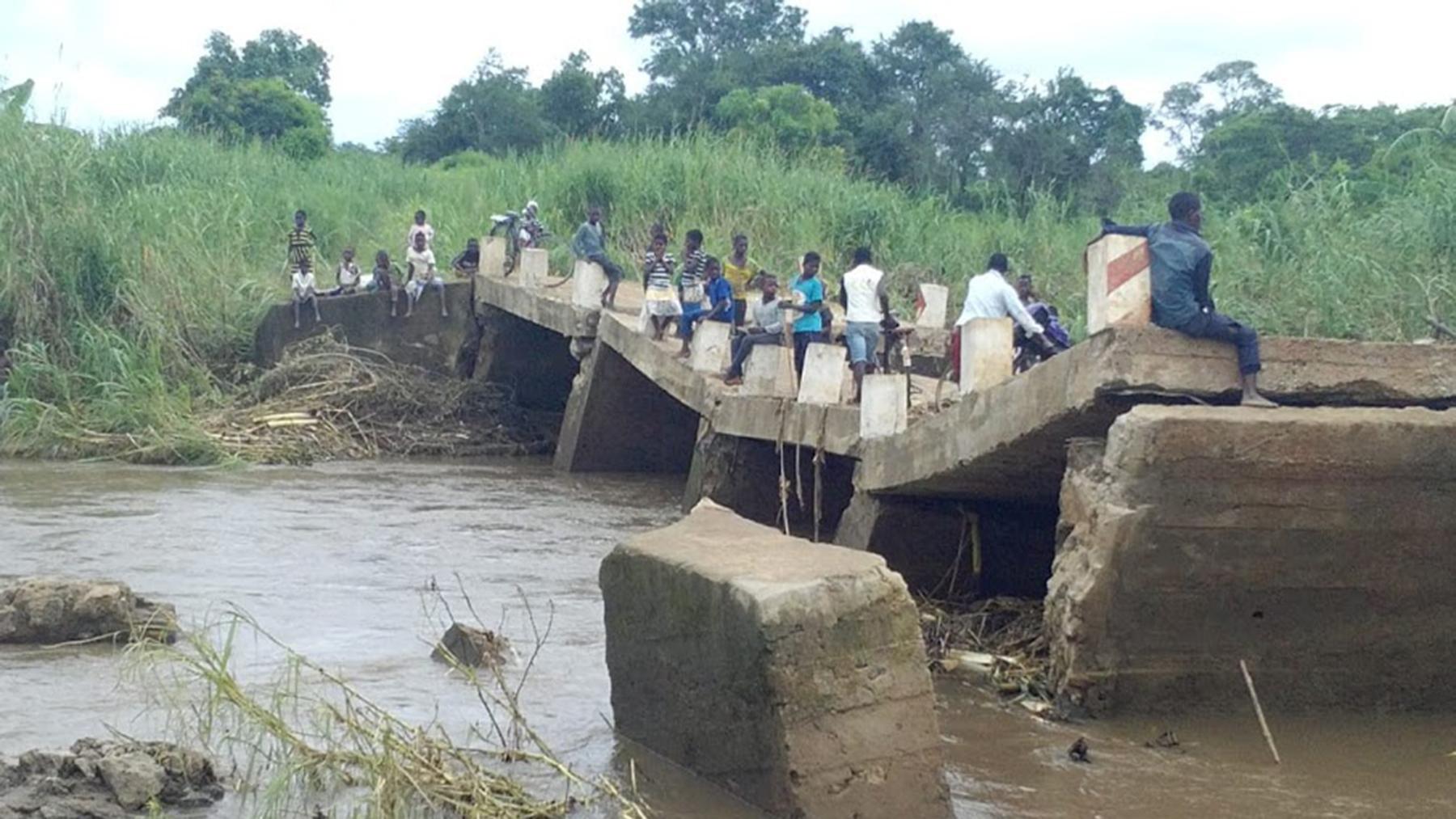 People cross a Cyclone Idai-damaged bridge in Zambezia Province, Mozambique. (Photo courtesy of the Real Medicine Foundation)