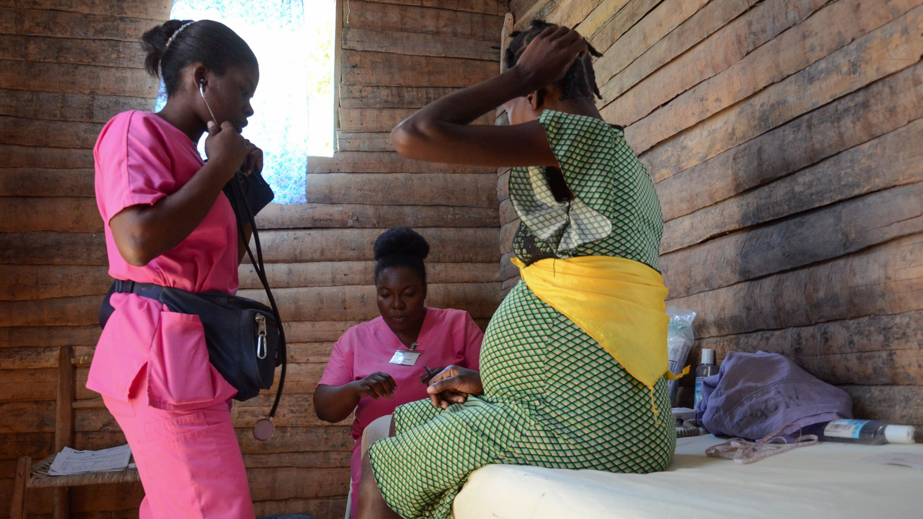 Midwives from the group, Midwives for Haiti, examine a patient during a prenatal visit. (Photo by Phalonne Pierre Louis/FotoKonbit)