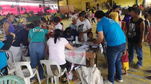 Health care workers take notes on people seeking medical care at an evacuation center in Banaba, Philippines. (Photo courtesy of Rebecca Galvez Tan)