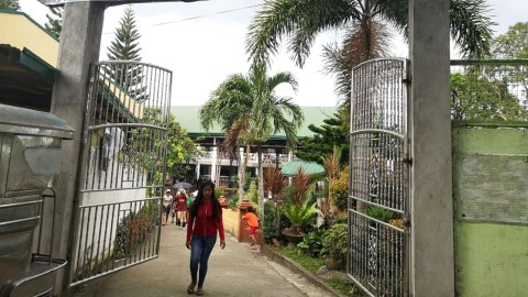 A young girl walks through the gates of the high school serving as the Pansol evacuation center. (Photo courtesy of Rebecca Galvez Tan)