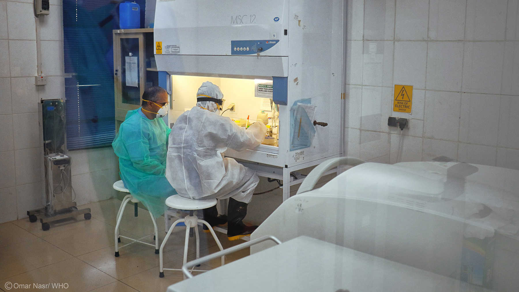Health care workers conduct a laboratory test. (Photo courtesy of the World Health Organization)