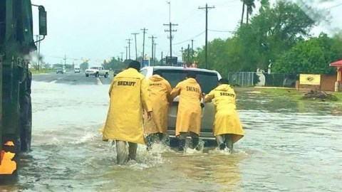 Hidalgo County Sheriff's Department staff push a vehicle through a flooded street. (Photo courtesy of the Hidalgo County Sheriff's Department)