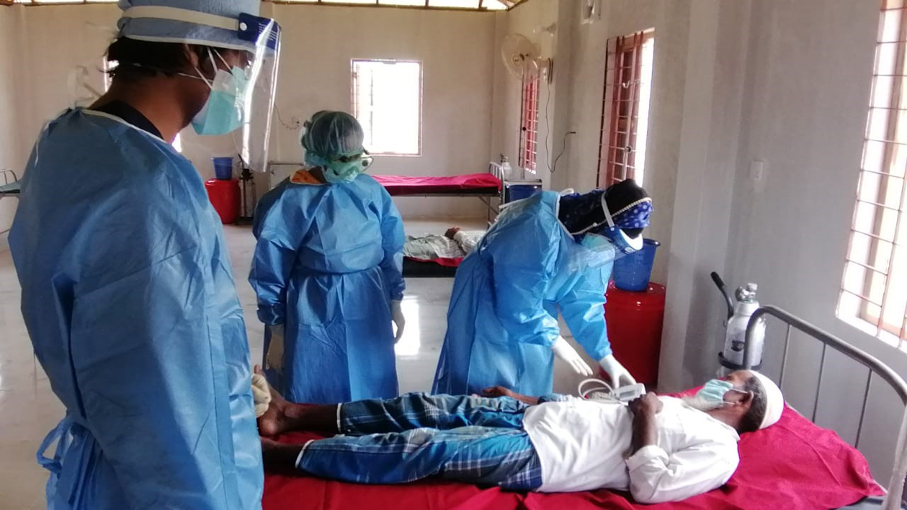 Staff members at the Covid-19 isolation center examine a patient. (Photo courtesy of HOPE for Bangladesh)