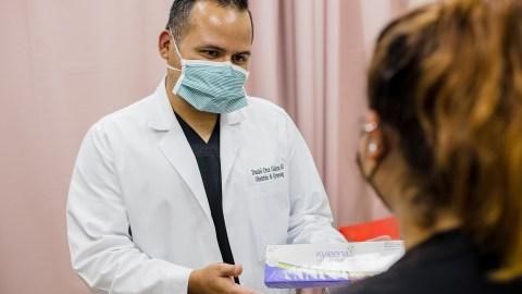 El Dr. Daniel Cruz Galarza, proveedor de atención médica de COSSMA, un centro de salud calificado a nivel federal, en Cidra, Puerto Rico, consulta con un paciente el 10 de diciembre de 2020. COSSMA se encuentra entre los cientos de centros de salud comunitarios en los EE. UU. que recibieron DIUs donados por Bayer para reforzar los servicios de salud reproductiva para mujeres sin seguro. (Foto de Gabriel González para Direct Relief)