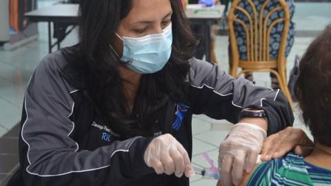 Una enfermera del Cuerpo de Reserva Médica vacuna a un paciente contra el Covid-19 en el Centro Cultural Yolanda Guerrero en Guaynabo. (Ana Umpierre/Direct Relief)