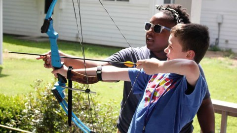 A camp staffer at the Center for Courageous Kids teaches an archery lesson to a camper. The center provides a summer camp experiece to medically fragile campers in Scottsville, Kentucky. Over the past week, Direct Relief shipped diabetes management supplies and hemophilia medications to the camp to support their efforts. (Courtesy photo)