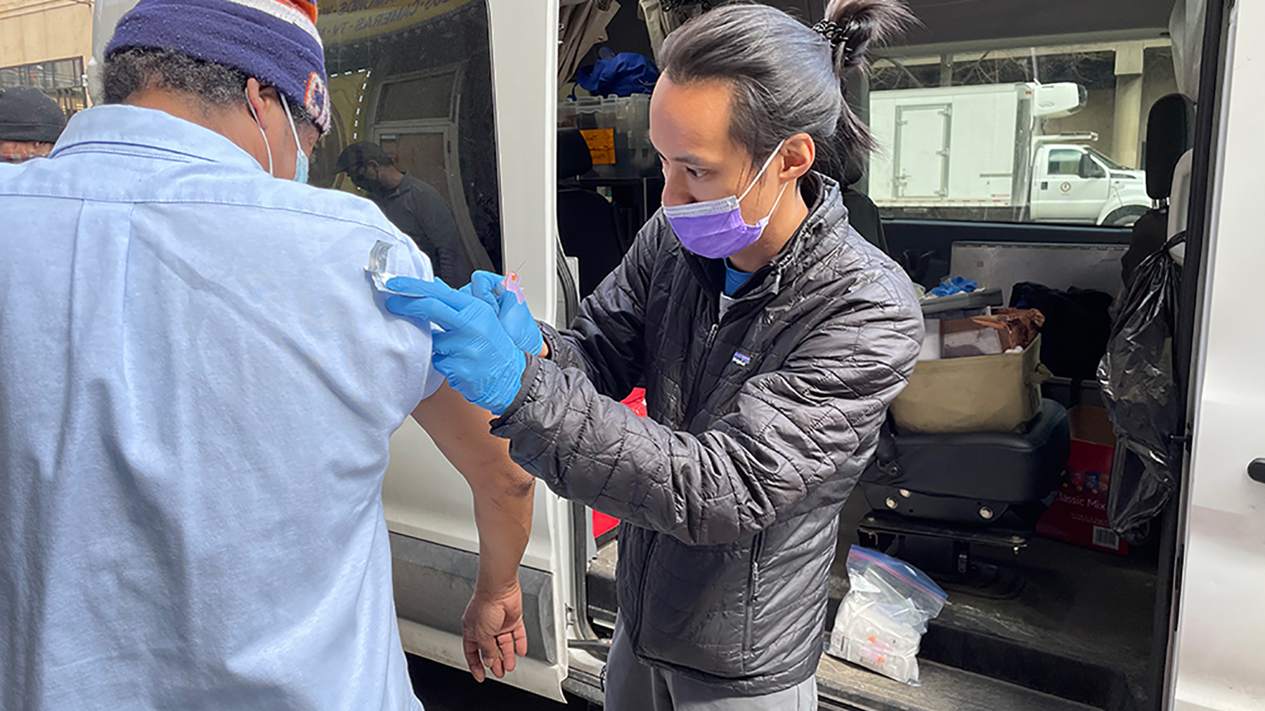 Dr. Nathan Lin (right), a medical resident, prepares a Covid-19 vaccine for a street medicine patient. Lin works with the Night Ministry, which provides health care and supportive services to Chicago's unsheltered homeless population. The organization received financial support from the Fund for Health Equity to expand its efforts. (Courtesy photo)