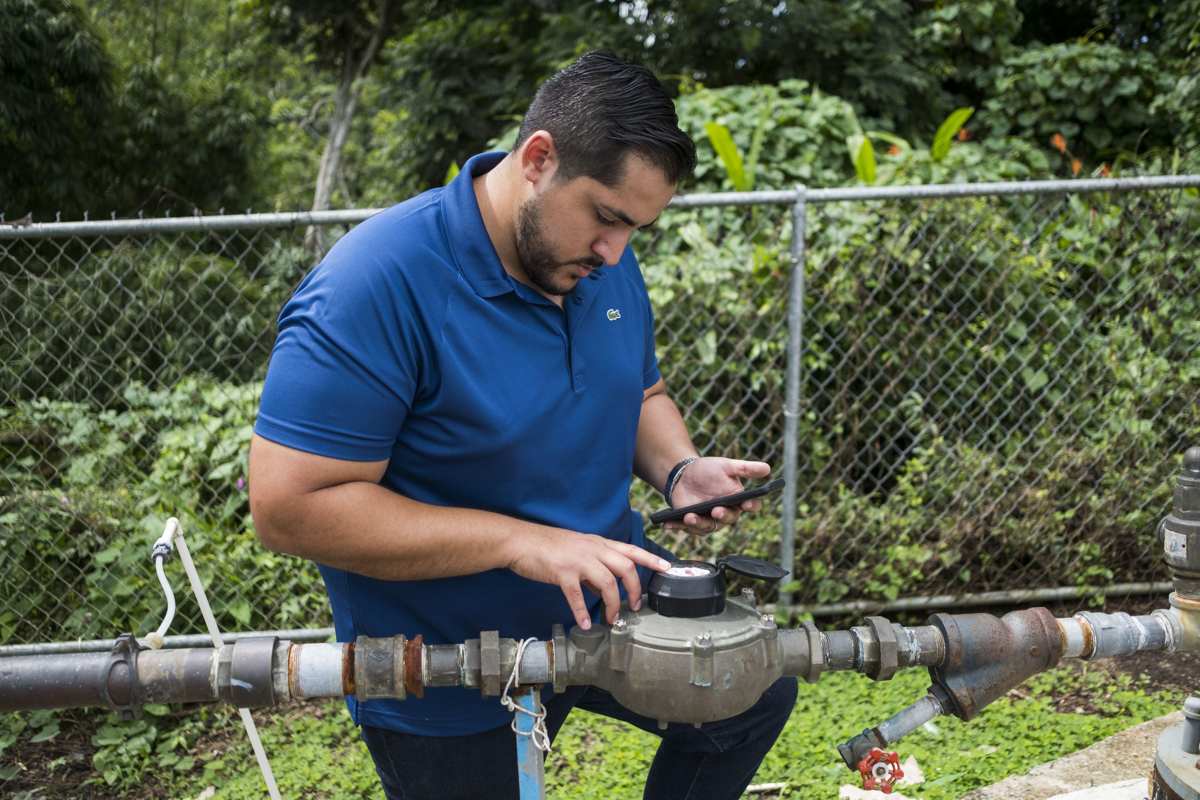 Alex Rodríguez, un joven estudiante de doctorado oriundo de Canovanas, Puerto Rico, verifica la presión del agua en la comunidad de Tejas, en Yabucoa, donde se instalaron paneles solares para suministrar energía al sistema de bombeo de agua de la comunidad. (Foto de Dennis M. Rivera Pichardo para Direct Relief)