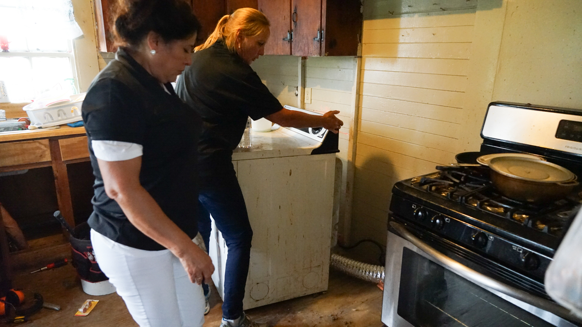 Nurse Gena Byrd and case worker Imelda Moye, both of whom conduct medical outreach for local farmworkers for Greene County Health Care, work to remove flood-damaged wood in the home of an elderly patient in Snow Hill, North Carolina. (Lara Cooper/Direct Relief)