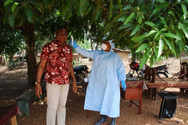 A midwife checks a visitor's temperature before he enters the Peripheral Health Unit in Makeni, Sierra Leone. The healthcare providers at this facility wear peronal protective equipment which was donated by Direct Relief, including surgical gown sets from Japan.