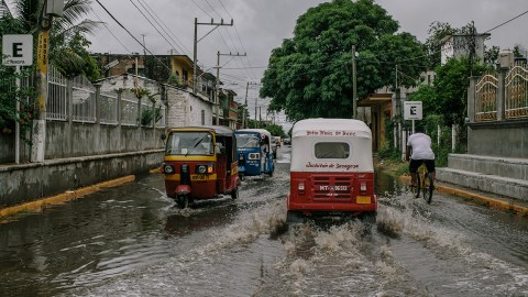 Vehicles plow through flooded streets on Thursday. (Photo by Meghan Dhaliwal for Direct Relief)