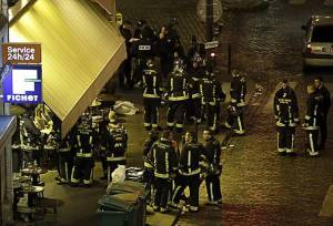 Police and rescuers are seen outside a cafe-brasserie in10th arrondissement of the French capital Paris, on November 13, 2015. At least 18 people were killed in a series of gun attacks across Paris, as well as explosions outside the national stadium where France was hosting Germany. Police said at least 15 people had been killed at the Bataclan concert hall in central Paris, only around 200 metres from the former offices of Charlie Hebdo which were attacked by jihadists in January. AFP PHOTO / KENZO TRIBOUILLARD (Photo credit should read KENZO TRIBOUILLARD/AFP/Getty Images)