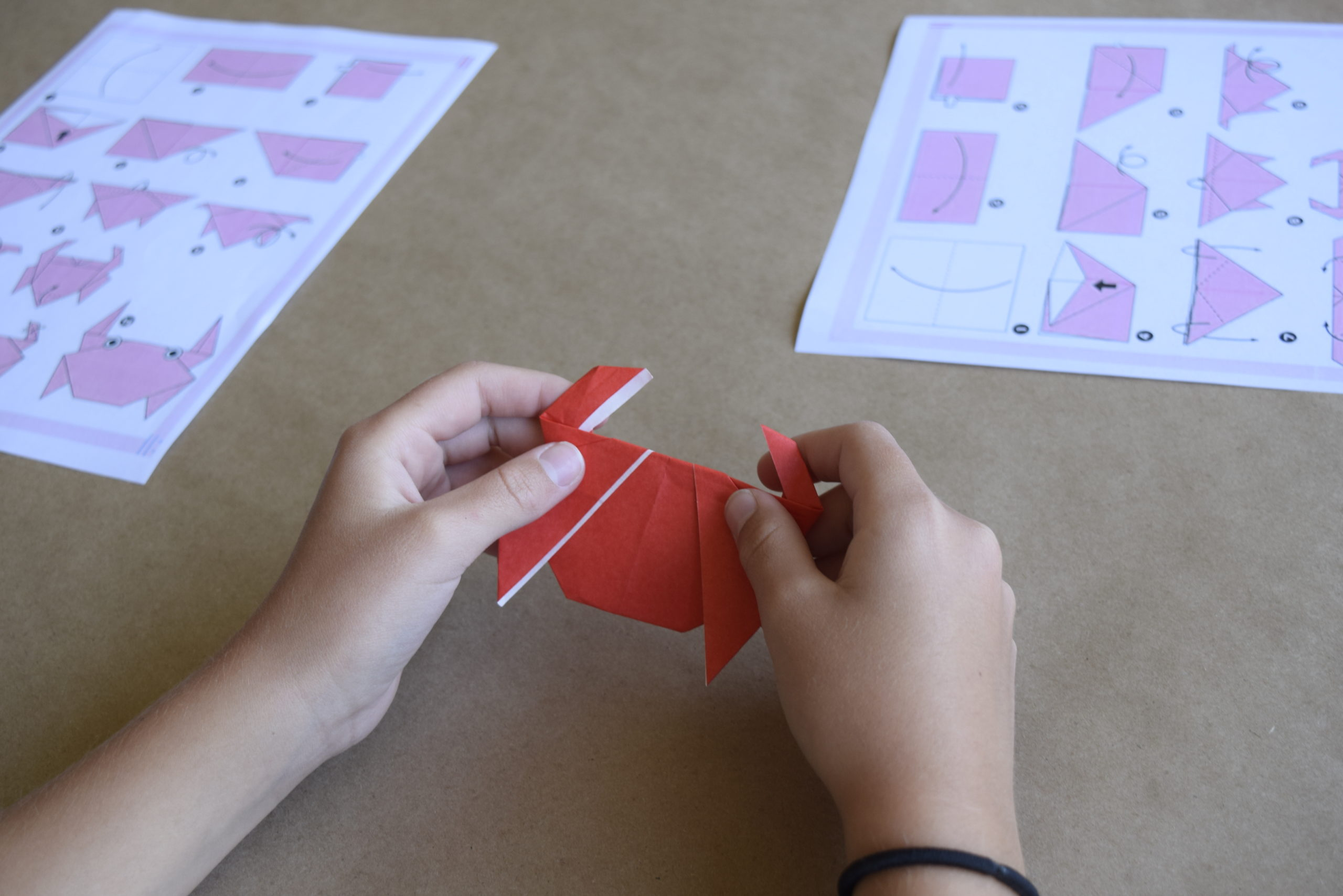A child's hand folds an oragami butterfly