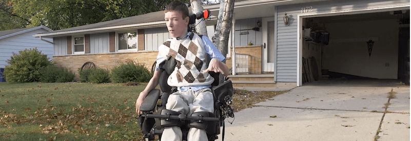 Trystan in his new wheelchair in the standing position in front of his house.