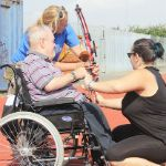 Man in wheelchair getting assistance to shoot a bow and arrow.