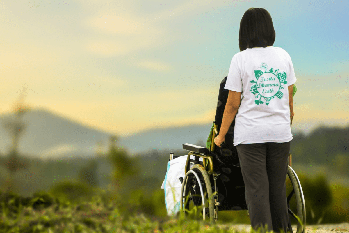 Woman pushing someone in wheelchair, facing outdoor scenery