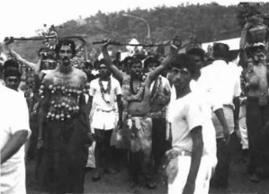 The head of the procession on its way to the temple. Some people hold  rope whips above their heads while others carry 'goron gons '.  (Photograph: AlIfhor·s collenioll)