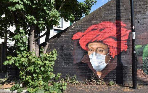 Un uomo con un turbante viene dipinto su un muro munito di mascherina anti-covid, a significare che la pandemia interessa ogni popolo della Terra