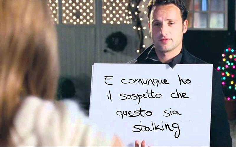 """Per illustrare il rapporto tra amore e stalking abbiamo scelto questo: una parodia della scena dei cartelli di Love actually. Sul cartello c'è scritto """"E comunque ho il sospetto che questo sia stalking"""""""