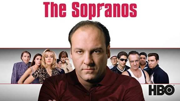 psicologia e serie tv : Tony Soprano in primo piano sotto la scritta/brand The Sopranos in secondo piano la Famiglia