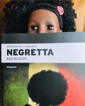 """Una bambola mostra il libro """"Negretta - Baci razzisti"""" di Marilena Delli Umuhoza"""