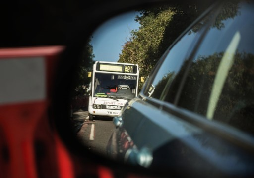 Reflection of a bus in a wing mirror of a car