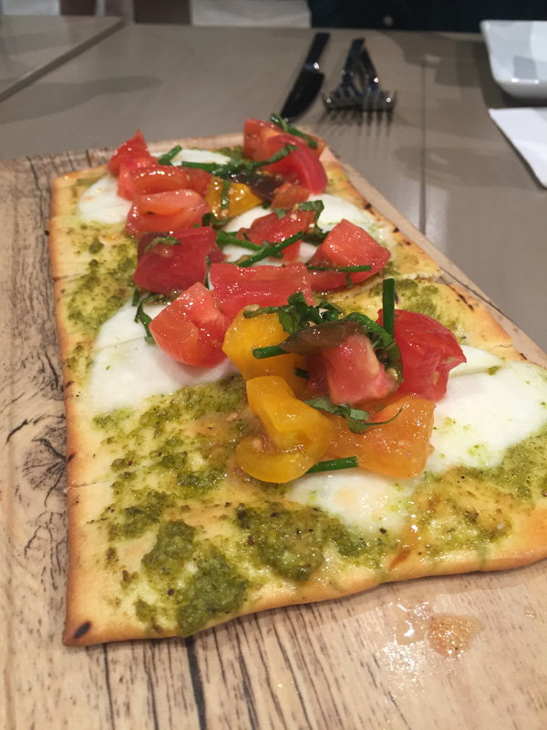 Flatbread spread with pesto and topped with fresh mozzarella, basil, chives and tomato salad