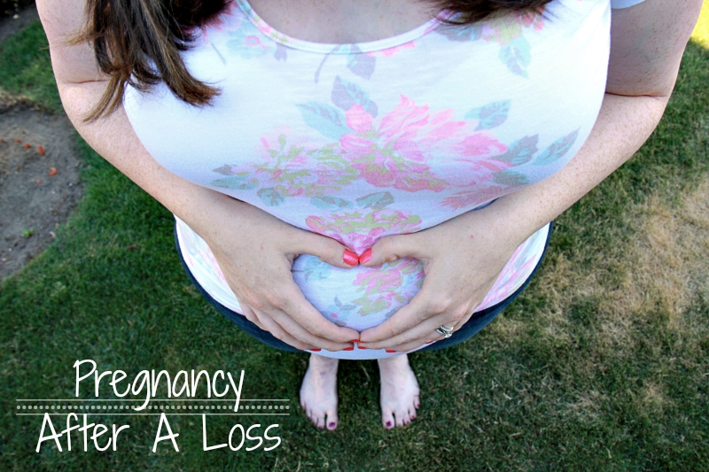 Pregnancy after a loss. Picture of pregnancy mother holding her belly with hands in a heart shape.