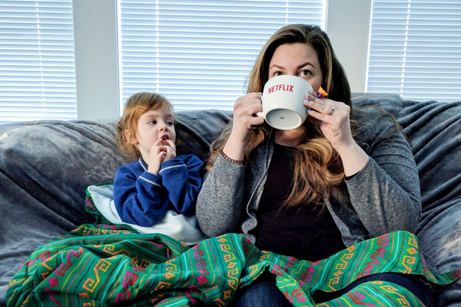 netflix sick day, mother and daughter sitting on the couch, mom is drinking from a Netflix mug