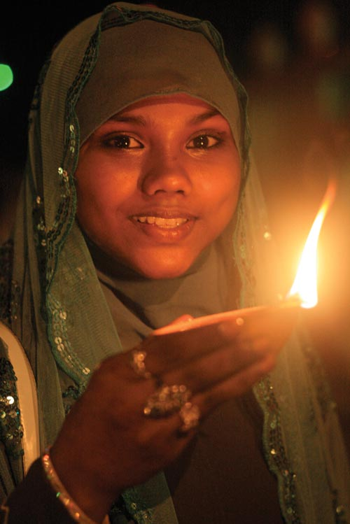 Lighting Divali deyas in Felicity. Photographer: Edison Boodoosingh