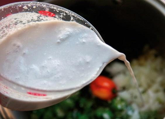 Add coconut milk to callaloo. Photograph by Ria Birju