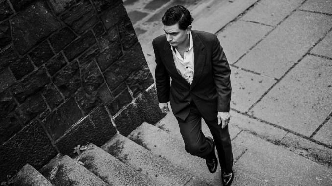 Svarthvit bilde av Luke Elliot som går opp en steintrapp