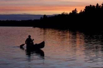 Man canoeing at sunset on northern Minnesota lake