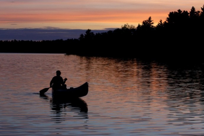 Man canoeing at sunset on northern Minnesota lake