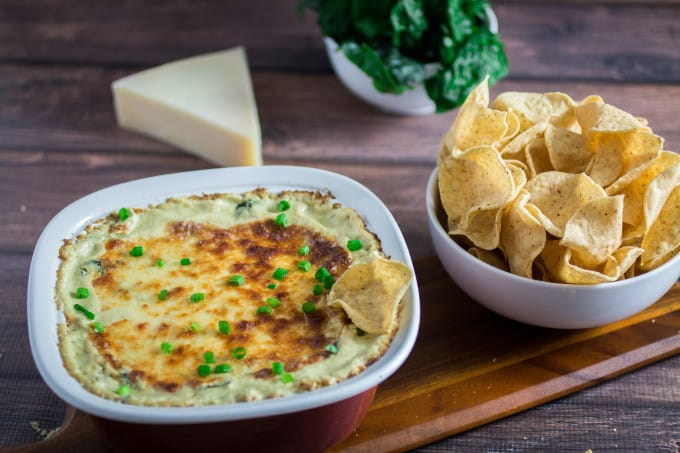 Cheesy, rich, and comfortingly creamy, it doesn't get much better than this classic Spinach Artichoke Dip. Topped with mozzarella cheese and baked to perfection, this dip recipe can be served with tortilla chips or a toasted baguette. You may want to make extra, this is one flavorful party food that won't last long once it's on the table!
