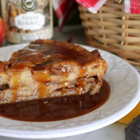 This Apple Brioche Bread Pudding is the perfect Autumn comfort food. Buttery Brioche bread and sweet apples are baked together with warming spices then served with a rich Apple Brandy Caramel Sauce. #breadpudding #briochebreadpudding #caramelsauce #falldessert #applebrandycaramel