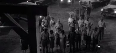 Screenshot from Twilight Zone. A crowd of people at night waiting for a hanging.