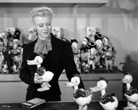 Ginger rogers arranging a row of toy ducks