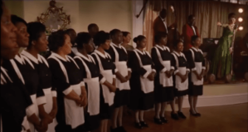 Black women holiday workers in maids uniforms lined up at a party next to a white woman in an evening gown