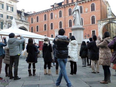 turisti che fotografano il monumento di dante in piazza dei signori a verona