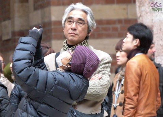 Turista giapponese fotografa con cappello viola e mascherina, nel centro storico di Verona