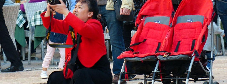 turista a verona che fotografa accucciata vestita in rosso e nero e carrozzina per gemelli