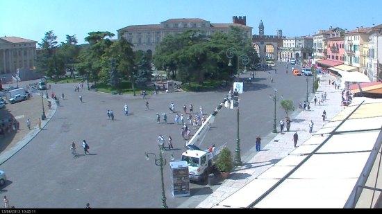 dalla webcam di piazza bra a verona il momento in cui vengono affissi ai  lampioni del liston i manifesti del centenario dell'arena di verona