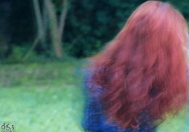 ragazza con i capelli rossi di spalle al lazzaretto di verona