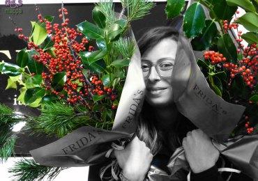 Camilla del negozio di fiori Frida's ritratta con le composizioni natalizie fatte per me